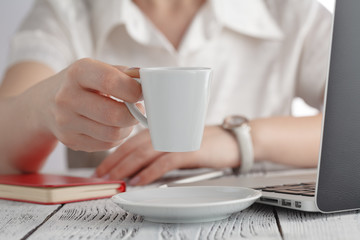 Female hands holding  cup of coffee closeup. Mobile computer Popular gadget, modern lifestyle, business life, morning coffee concept