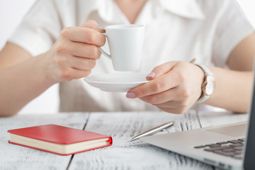 Female designer hands holding cup of hot beverage and working with laptop. Employee woman drinking morning tea of coffee. Coffeebreak during working day, creative people