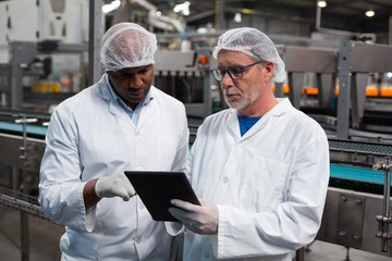 Two factory engineers discussing over digital tablet