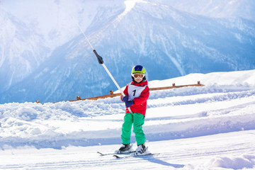 Young skier using a surface lift on the slope
