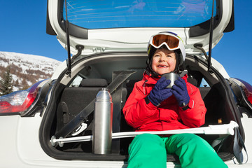 Boy skier sitting in car boot and drinking tea