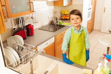 Boy cleaned all the dishes in kitchen sink
