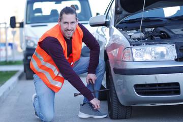 Mann in Warnweste bei seinem liegengebliebenen Auto