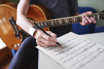 a person making notes on sheet music and holding a guitar.