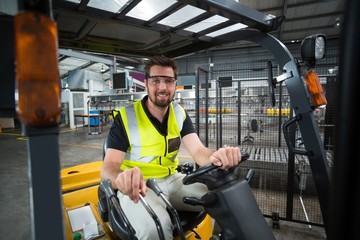 Portrait of smiling factory worker driving forklift
