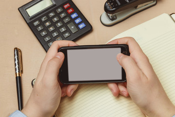 Closeup of a man pointing finger to smartphone with a blank screen monitor