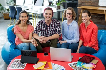 Smiling graphic designers sitting in office