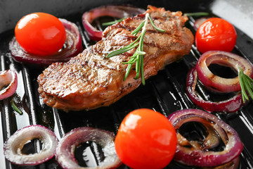 Delicious grilled steak with aromatic rosemary, tomatoes and onion rings on pan, closeup