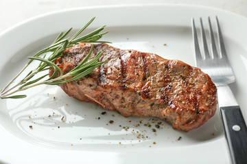 Wall Mural - Delicious grilled steak with aromatic rosemary on white plate, closeup