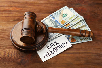 Card with text TAX ATTORNEY, judge's gavel and dollar banknotes on wooden background