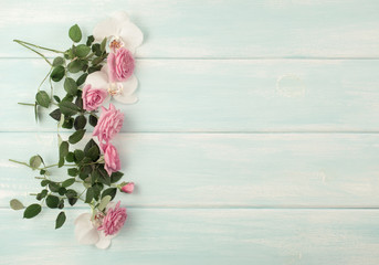Wooden background with roses and orchid flowers