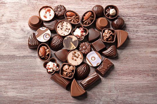 Heart-shaped collection of chocolate candies on wooden background