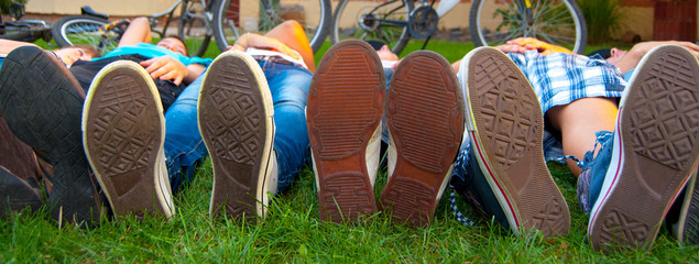 Feet and sneakers of teenage boys and girls lying in the grass after bicycle ride on sunny spring day