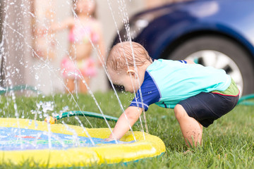 Child, boy or kid plays with water sprinkler toy outdoors during summer or spring to cool off in hot weather