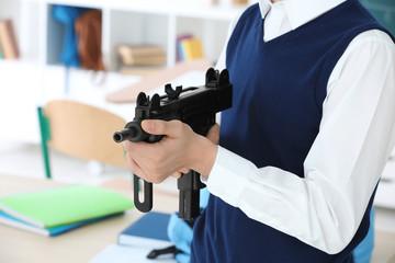 Closeup of schoolboy holding machine gun in classroom