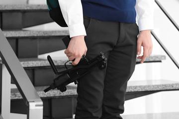 Schoolboy with machine gun in hand standing on stairs