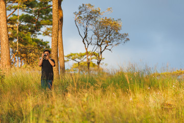 Man taking photos of landscape in the forest at Phu Soi Dao, Uttaradit, Thailand.