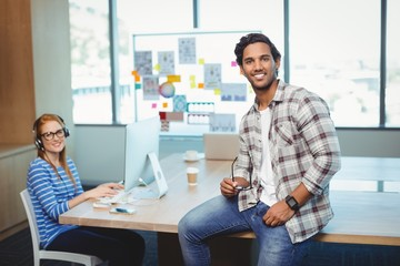 Male sitting on desk with coworker in conference