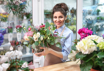 Beautiful woman florist holding pot with flowers in flower shop