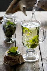 Cup of fresh herbal tea (Dried wintergreen) on wooden table. The frozen movement. Selective focus.