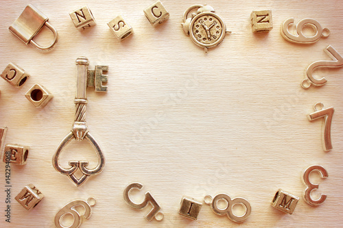 old vintage metal key in frame from different metal letters and numbers with copy space