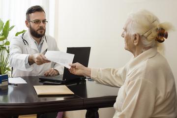 Fototapeta Lekarz podaje zastrzyk w brzuch starej kobiecie. Lekarz geriatra przyjmuje pacjenta w gabinecie. Stara kobieta u lekarza geriatry.Lekarz geriatra przyjmuje pacjenta. Odbiera dokumenty od pacjentki. obraz