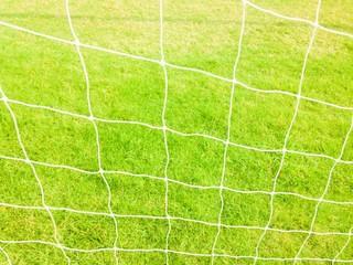 Soccer football net with green grass background