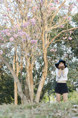 beautiful Asian girl with pink flower tree, natural site
