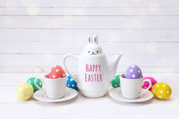 Kettle-hare with with message Happy Easter, cups and eggs on a white background.