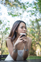 Young woman holding disposable coffee cup while sitting enjoying at nature outdoors.