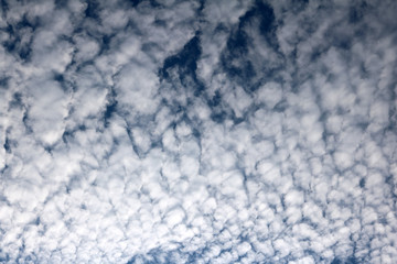 Pattern of white clouds streaming by wind with blue sky background