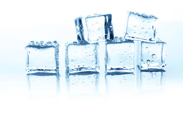 Transparent ice cubes group on white background with water drops