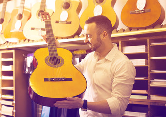 Guy choosing guitar in music shop.