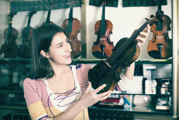 Teenage girl selecting classical violin