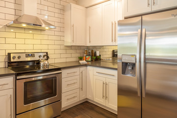 contemporary white kitchen with subway tiled walls and chrome appliances