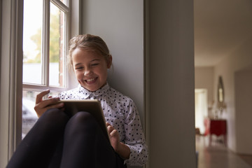 Smiling girl using tablet computer while sitting near window at home