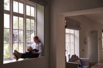 Girl Sits By Window At Home Using Digital Tablet