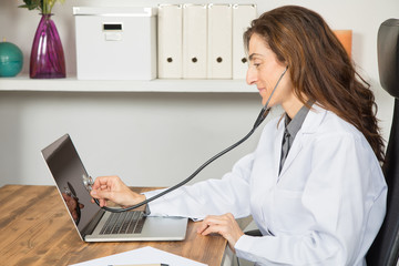side view of brown hair doctor woman, with white gown sitting, showing stethoscope to screen of portable laptop computer, as auscultating or checking, on wooden table office