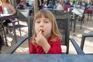 portrait of blonde three years old child face, with red shirt, eating cheese puff, with crumbs in mouth, sitting in terrace exterior bar cafe with grey table in park
