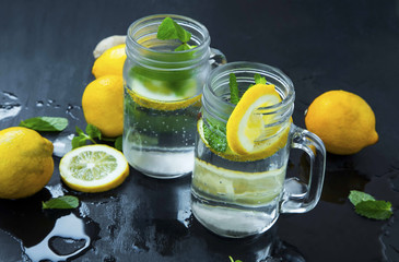Fresh lemon infused water or soda drinks in glasses with mint, lemons and ice cubes