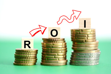 Return on investment analysis with ROI text on wooden cubes on top of upward stacked coins
