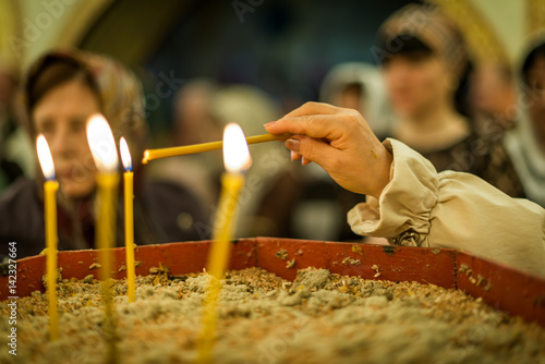The parishioner's hand reaching out to the candle in order