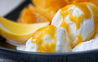white ice cream with a sauce of ripe mango fruit