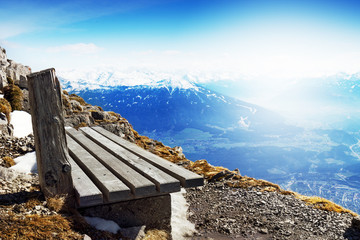 Travel or Vacation Concept. Wooden Bench behind Beautiful Mountain Landscape. Blue Sky. Alps, Austria.