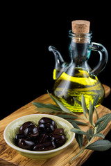 Black olives, bottle of virgin olive oil and olive branch on wooden chopping board and black background