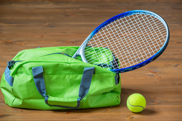 A tennis racket sticks out of a green sports bag, objects on the floor