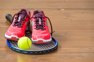 Pair of women's sneakers on a tennis racket on a wooden floor