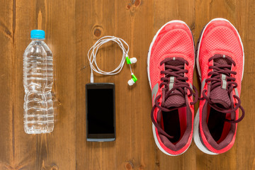 bottle of water, telephone and running shoes for sports on a dark wooden floor view from above close up