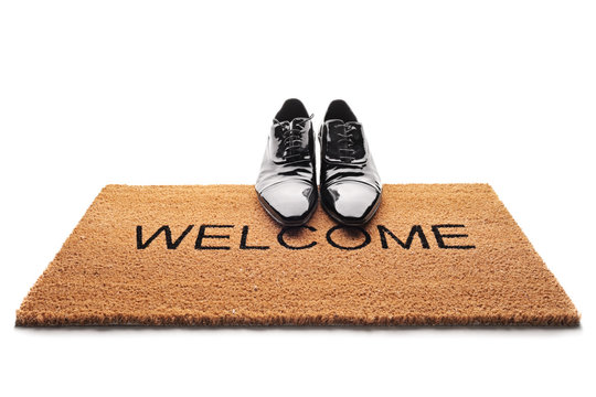 Shoes on a doormat with the word welcome