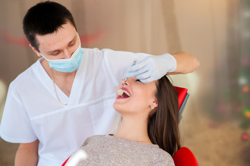 The dentist is treating teeth with a beautiful girl.